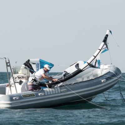 Adrenalins-Instruktor startet Kite vom Boot aus am Gardasee